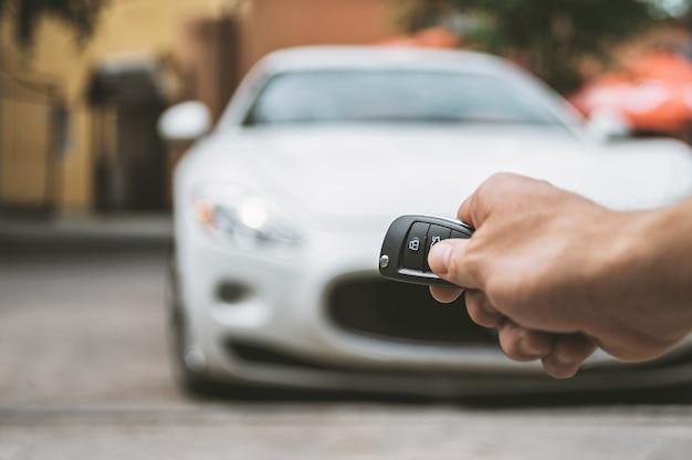 De man opent de auto met een sleutelhanger