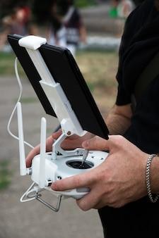 De man-operator houdt een bedieningspaneel voor de drone vast met een tablet