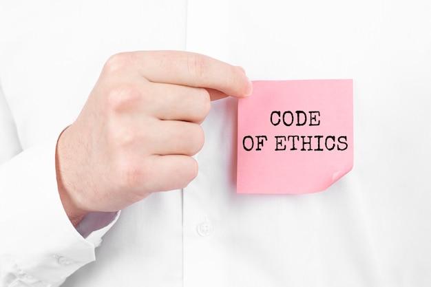De man plakt een rode sticker met de tekst code of ethics op zijn witte overhemd