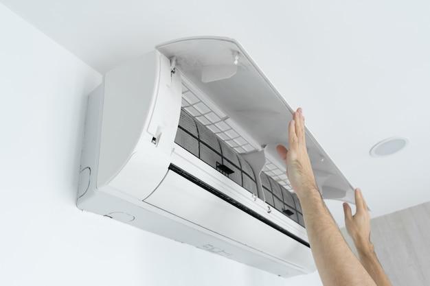 De man reinigt het filter van de airconditioner thuis van stof.