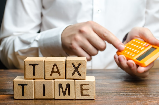 De man rekent op de calculator de benodigde belastingbetaling. belastingen, inkomstenbelasting