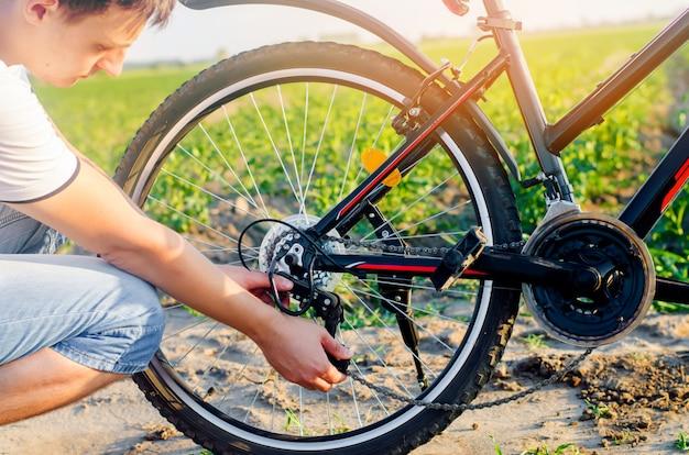 De man repareert de fiets. kettingreparatie. fietser. onvriendelijkheid op de weg, reizen, close-up.