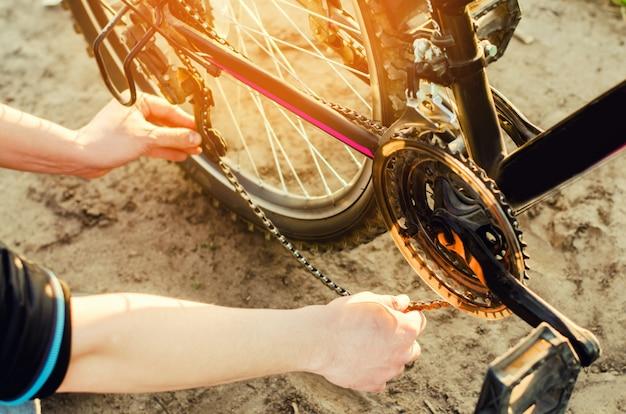 De man repareert de fiets. kettingreparatie. fietser. onvriendelijkheid op de weg, reizen
