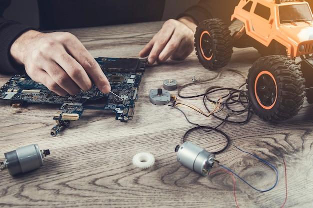 De man repareert speelgoedauto en bord