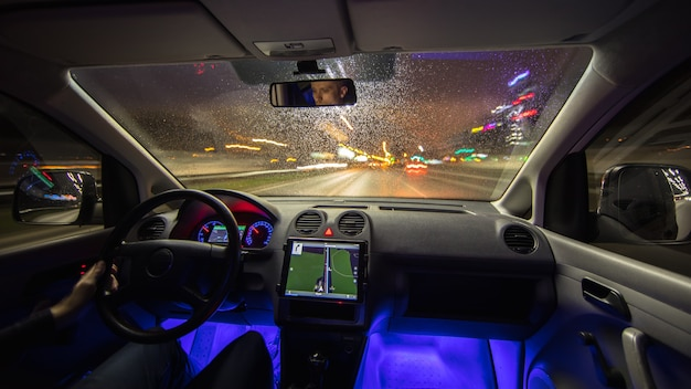 De man rijdt auto in de regenachtige stad. avond nacht tijd