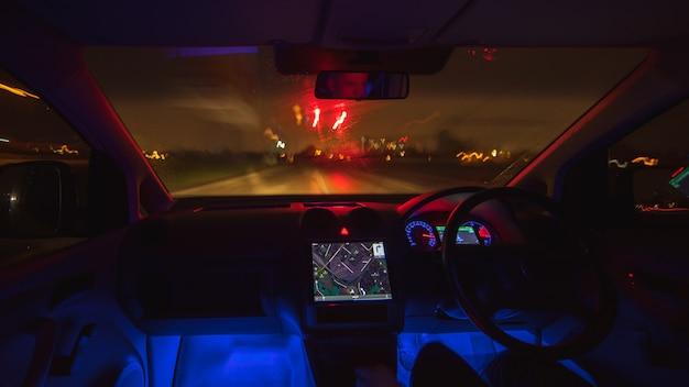 De man rijdt met een kaart op een regenachtige stad. avond nacht tijd. links verkeer