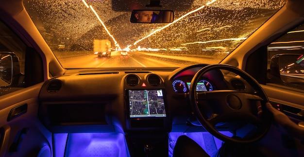 De man rijdt met navigatie in de regenachtige stad. avond nacht tijd