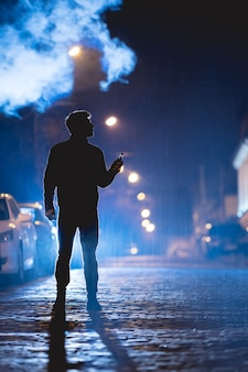 De man rookt elektrische sigaret op straat. avond nacht tijd