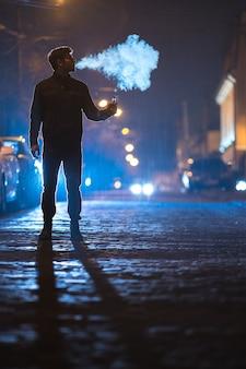 De man rookt elektronische sigaret op straat. avond nacht tijd