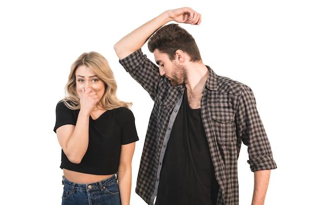 De man ruikt oksels bij de vrouw op de witte achtergrond