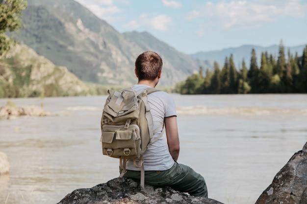 De man rust uit aan de rivier