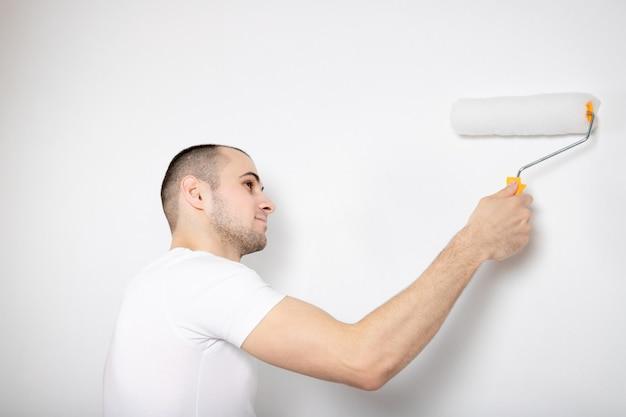 De man schildert de muur met een bouwrol.