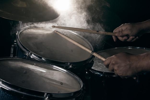 De man speelt drumstel.