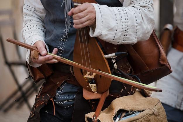 De man speelt een rebec-instrument