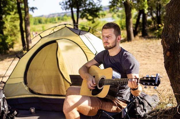 De man speelt gitaarmuziek bij de tent op een klapstoel in het bos