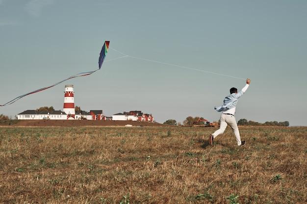 De man speelt met een vlieger in het veld. vuurtoren op de achtergrond. herfsttijd, buitenspellen.