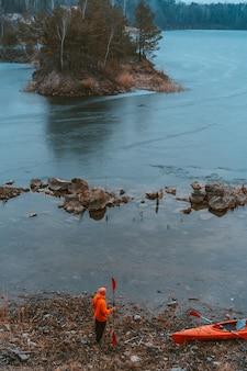 De man staat bij het bevroren meer