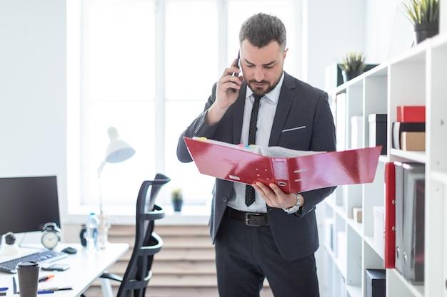 De man staat in de buurt van het rek op kantoor, telefonerend en houdt een map in zijn hand.