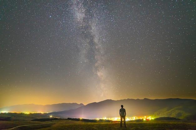 De man staat op de achtergrond van de stadslichten. nachttijd
