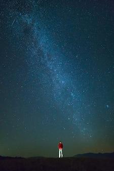 De man staat op de achtergrond van de sterren. nachttijd