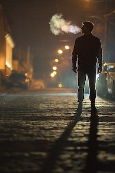 De man staat op de regenweg. avond nacht tijd. telelens opname
