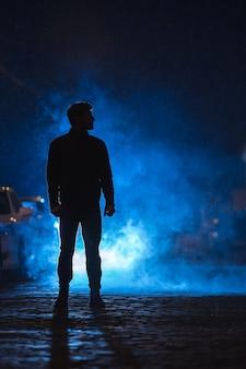 De man staat op de rokerige straat. avond nacht tijd
