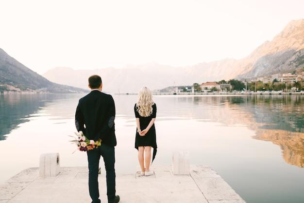 De man staat op het punt zijn vriendin te verrassen met een bos bloemen en een huwelijksaanzoek