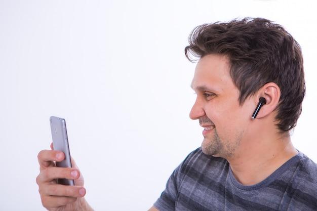 De man stopt een draadloze koptelefoon in zijn oor en begint te telefoneren via een videoverbinding. mens en moderne technologieën. naar muziek aan het luisteren