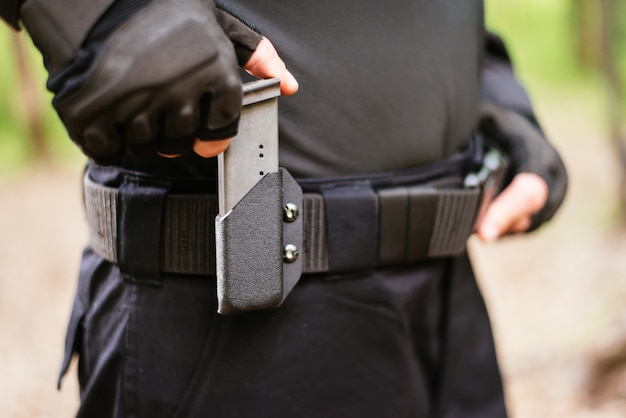 De man stopt een tijdschrift uit het pistool in zijn holster