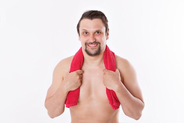 De man streelt zijn baard. ochtendbehandelingen in de badkamer. blauwe handdoek om haar nek. geïsoleerd op een witte achtergrond. kopieer ruimte