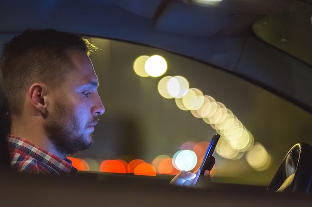 De man telefoon in de auto op de snelweg. avond nacht tijd