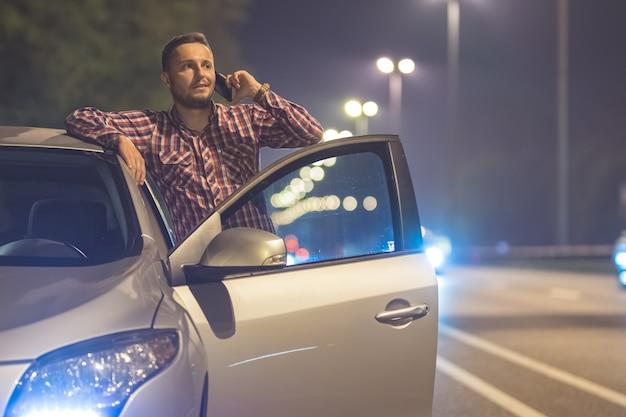 De man telefoon in de buurt van de auto op de weg. avond nacht tijd