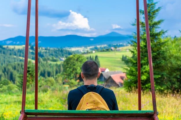 De man-toerist zit op de schommel en geniet van het adembenemende natuurlandschap van de zomerse karpaty-bergen.