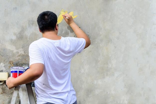 De man van asian die een wit t-shirt draagt, gebruikt zijn penseel om iets op de cementmuur te tekenen.