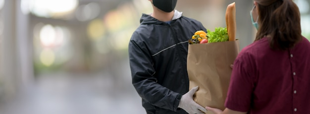 De man van de de leveringsdienst van het voedsel leverde verse voedselzak aan jonge vrouwelijke klant bij haar thuis