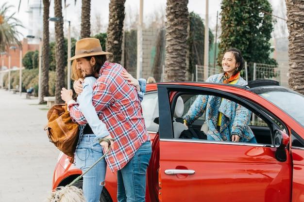 De man van de jonge manengroet dichtbij rode auto