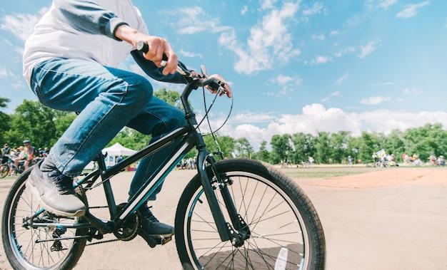 De man van hipster fietst bij zonnig zomerweer. wandelen in het park op de fiets. close-up fiets.