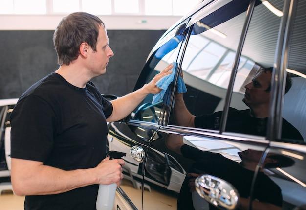 De man veegt af met een stoffen lijf van een schitterende auto.