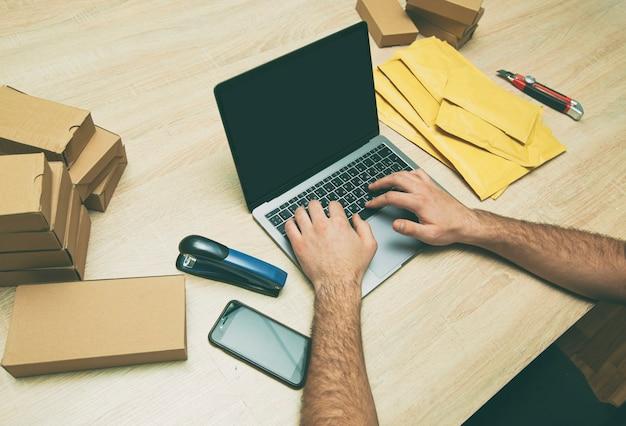 De man verpakt het product in de gele envelop