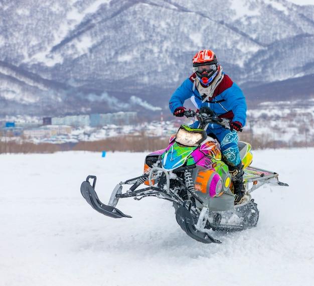 De man vliegt op een sneeuwscooter
