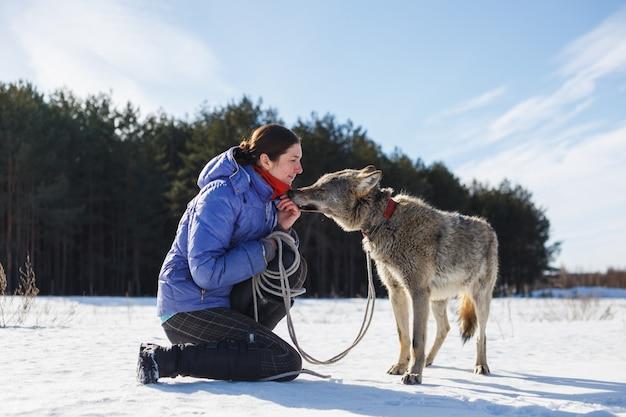 De man voedt zijn husky-hondenkoekjes buiten van mond tot mond