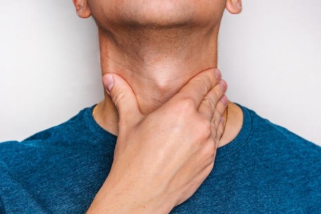 De man voelt keelpijn en controleert de amandelen en lymfeklieren