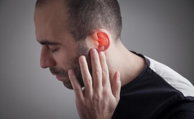 De man voelt oorpijn