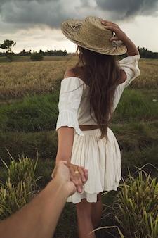 De man volgt haar vrouw. paar hand in hand in het rijstveld.