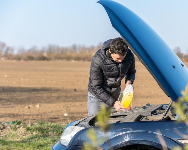 De man vult de ruitensproeiervloeistof bij