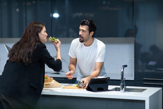 De man was aan het koken voor zijn vrouw, terwijl de vrouw zich haastte om te werken. gelukkige familie tijd samen doorbrengen thuis.