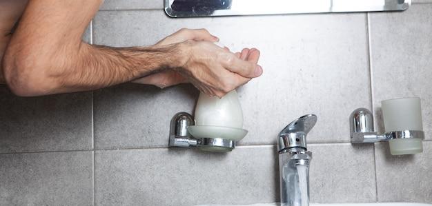 De man wast zich in de badkamer