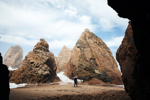 De man wervelt de vrouw en ze zien er erg gelukkig uit, een stel staat op het strand tussen de rotsen