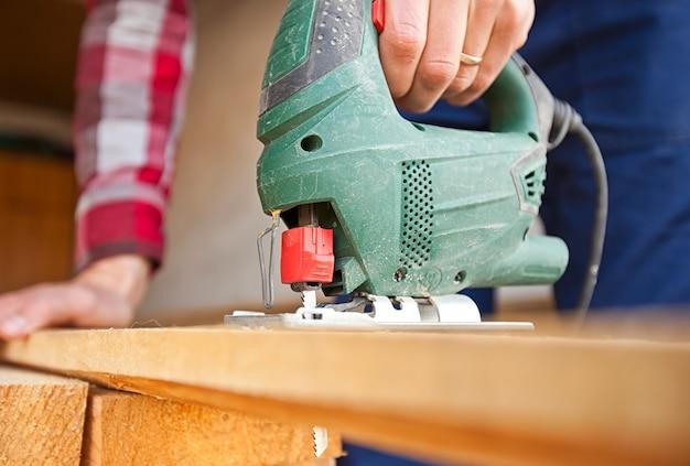 De man zaagt de houten plank met een decoupeerzaag
