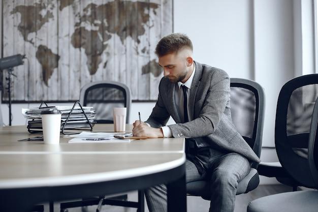 De man zit aan de tafel. kerel in een pak. zakenman ondertekent de documenten